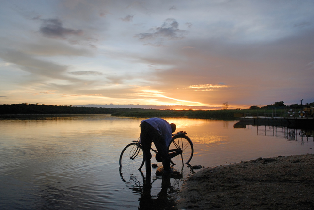 Man with bicycle at sunset